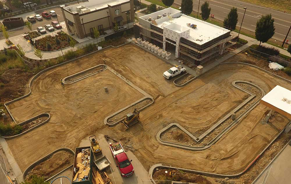 Drone view of construction sight with unfinished building and parking lot